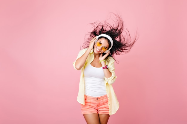 黒髪を振って笑ってポーズをとるカラフルな服を着たうれしいラテンの女の子。楽しんでいるヘッドフォンでアジアの女性モデルを喜ばせる