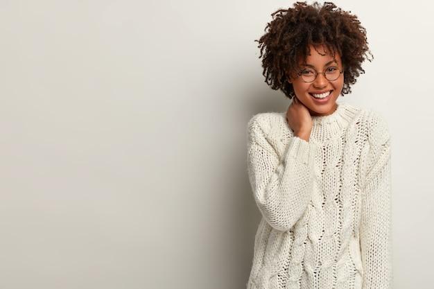 Довольно смеющаяся, кудрявая женщина хихикает, когда слышит анекдот, носит белый свитер, держит руку на шее, выражает положительные эмоции, стоит в помещении, пустое место прямо для вашей рекламы. счастье