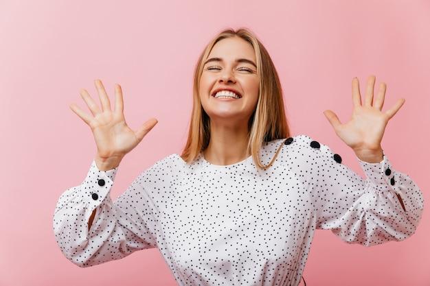 屋内で冷やしている白いブラウスでうれしい笑いの女性。ブロンドの髪を持つかなり身なりのよい女性の肖像画。