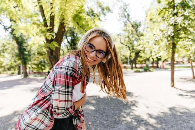 公園で音楽を楽しんでいるうれしい長髪の女の子。晴れた日に踊るヘッドフォンで華やかなブロンドの女性。