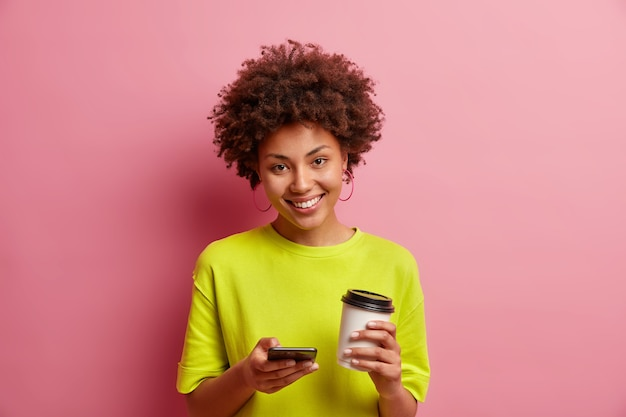 Радостная милая афроамериканка использует современный мобильный телефон для общения в чате, загружает новое приложение, тратит время в социальных сетях, пьет кофе на вынос, носит повседневную футболку, изолированную на розовой стене