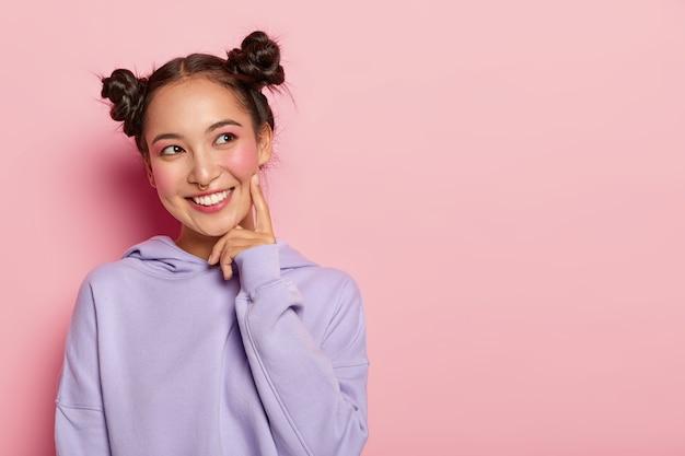 笑顔で嬉しい素敵な女性、人差し指を頬に保ち、脇を見て、2つの結び目を持って、紫色のスウェットシャツを着て、元気になっています