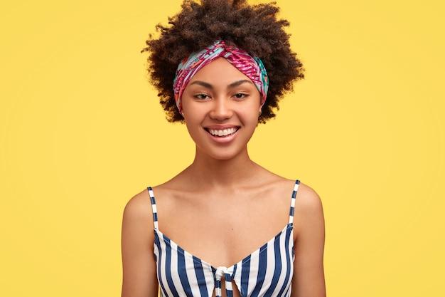 Радостная милая женщина с зубастой улыбкой, одетая в полосатую футболку, повязку на голову, выражает позитив