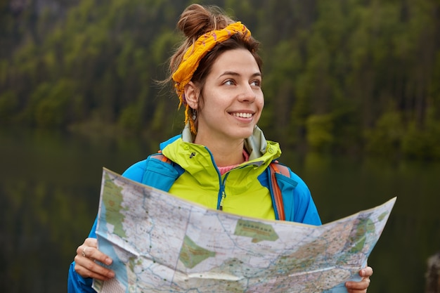 Glad lovely young female traveler chooses best way for destination, plans route during journey, holds map, looks away