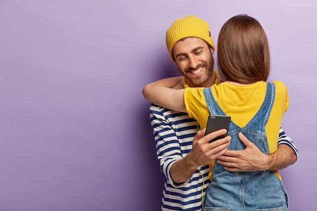 Радостный обманщик отправляет текстовое сообщение любовнику, обнимая жену, ведет секретный чат за спиной подруг, держит в руке современный сотовый телефон