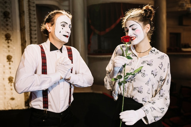 Glad male mime artist looking at smiling female mime smelling red rose