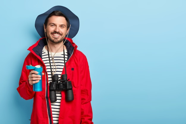 Glad male tourist holds blue thermos, drinks tea during travel, explores new place, wears casual clothes, carries binoculars, stands against blue wall