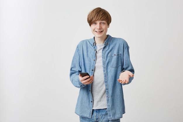 彼のスマートフォンが友達とチャットしている屋内で立っている金髪のうれしい男性。カジュアルな服装で肯定的な若い男が友人からのメッセージを受け取り、ジェスチャーを積極的に行い、笑顔で肩をすくめる