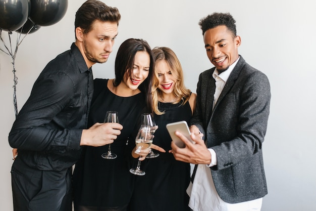 Glad man showing friends last photos on his phone during party