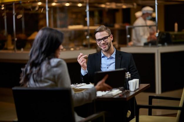 Довольный мужчина с короткой бородой в очках и с интересом смотрит на картинку на планшете, представленную деловым партнером