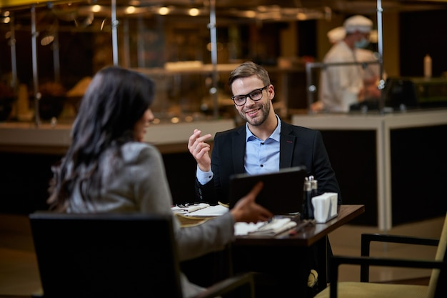 Glad man with short beard wearing glasses and looking with interest at picture on tablet, presented by business partner