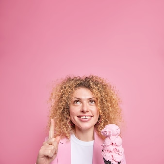 Glad merry curly haired young european woman concentrated above indicates at blank copy space holds delicious cone ice cream demonstrates advertising content eats summer dessert during weekend