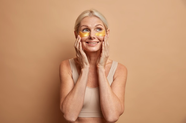 Радостная блондинка средних лет трогает лицо, нежно наносит коллагеновые косметические пятна под глаза, имеет мечтательное выражение