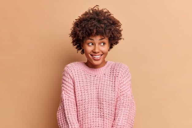 아프로 머리를 가진 기쁜 밀레 니얼 여성은 부드럽게 미소를 짓고 멀리 보이는 것은 베이지 스튜디오 벽 위에 고립 된 긍정적 인 감정을 표현합니다.