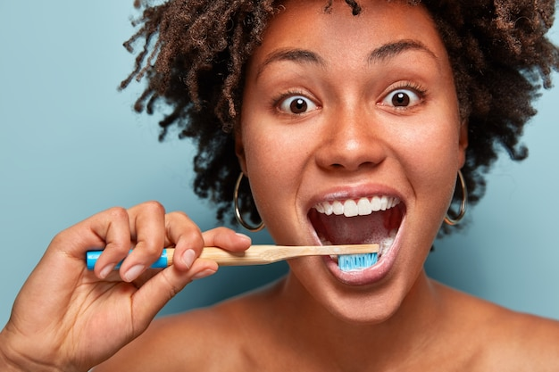Glad mirthful woman with dark healthy skin, satisfied with new toothpaste, cleans teeth, opens mouth widely, has happy expression, curly hair, models over blue wall. close up portrait.