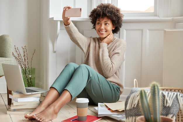 Glad mixed race woman with afro hairstyle, poses at cell phone for making selfie