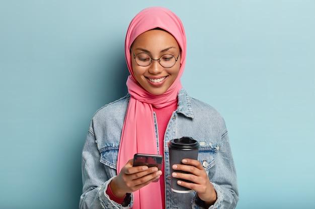 건강한 어두운 피부, 유쾌한 미소를 지닌 기쁜 혼혈 여성은 휴대 전화와 테이크 아웃 커피를 들고 분홍색 히잡 헤드 스카프, 데님 재킷을 입고 메시지를 수신하고 파란색 벽 위에 절연되어 있습니다.