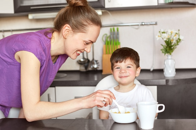喜んでいる母親は、小さなオスの子供にスプーンで食事を与え、おいしいお粥とお茶を与え、夕食後に散歩に行くことを約束し、台所の隣人に座ります。笑顔の若い女性は子供のための穀物を準備します。