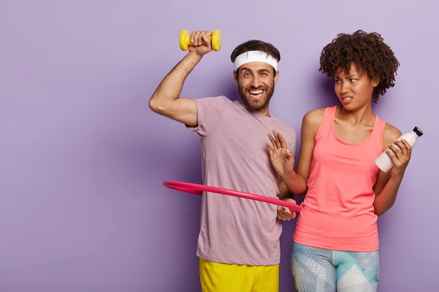 Glad motivated man with stubble, rotates hula hoop, trains muscles with dumbbell and dissatisfied afro woman makes refusal gesture, holds bottle of water