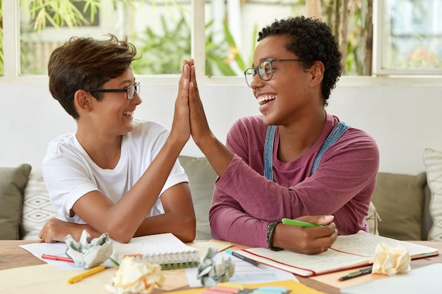 Glad multiethnic dark skinned woman and youngster give high five to each other, sit at workplace, achieve good results while study together, write records in notepad, demonstrate their agreement