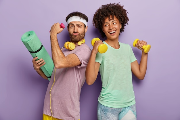 Glad multiethnic husband and wife attend sport center, exercise with dumbbells, hold fitness mat, stand back to each other, have funny happy looks, wear t shirts, isolated on purple wall