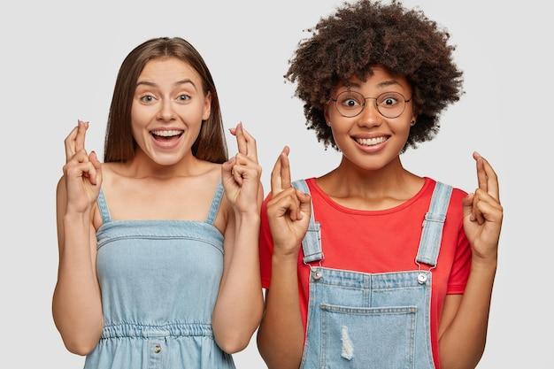 Радостные многонациональные женщины скрестят пальцы на удачу перед сдачей вступительных экзаменов