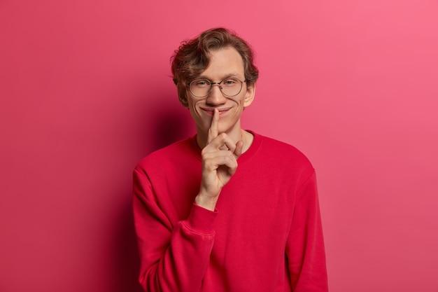 嬉しい神秘的な男性モデルは、沈黙の兆候または静けさのジェスチャーを示し、人差し指を唇に保ち、秘密を求め、情報を秘密に保つように伝え、ウェーブのかかった髪をし、真っ赤なセーターを着ています