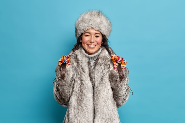 Glad northern woman holds pigtails and smiles broadly wears grey fur hat and coat poses indoor against blue wall