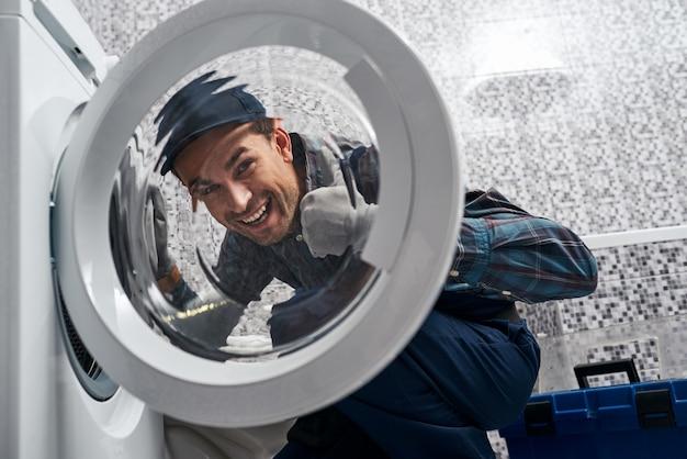 세탁 기계를 확인하는 욕실에서 일하는 남자 배관공의 결과에 만족합니다.