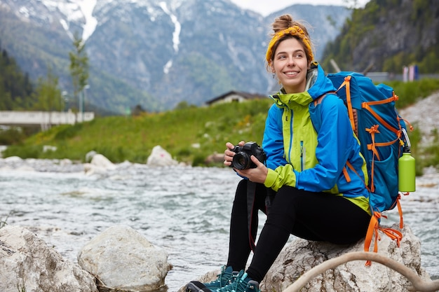 Glad optimistic female tourist rests outdoor on rock