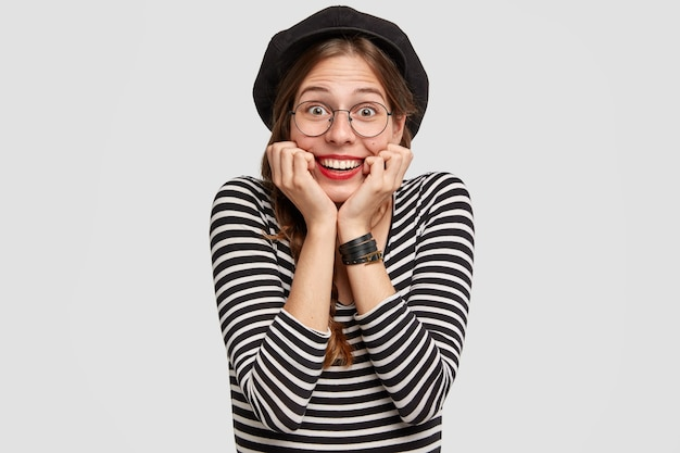 Glad parisian woman touches chin with both hands, has shining smile, cheerful facial expression, dressed in casual french style clothes