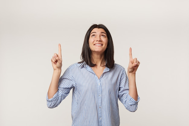 Glad pleased young dark-haired woman looks upwards with excitement and smile, keeps hands up and pointing with fore fingers above on copy space, dressed in a striped shirt,isolated on a white wall