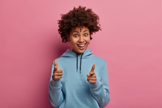 嬉しいポジティブなアフロアメリカ人女性があなたを指さし、広く笑顔
