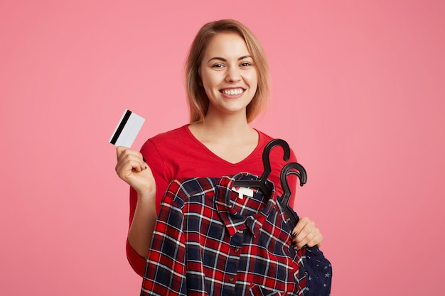 Glad positive female holds clothes on hangers and plastic card, going to pay for new purchase, enjoys going shopping with best friend, isolated over pink. people and payment concept