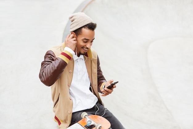 Радостный позитивный скейтбордист занимается экстремальным спортом, отдыхает минутку, слушает любимую аудиозапись в наушниках.