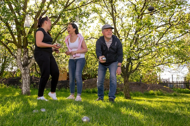 Glad positive smiling family playing french traditional game petanque in a garden outside during lovely summer day enjoying leisure time Premium Photo