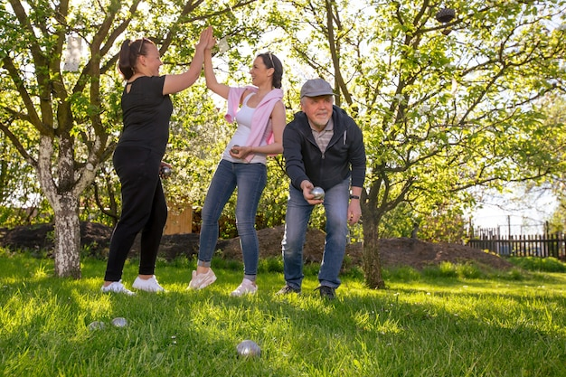 Glad positive smiling family playing french traditional game petanque in a garden outside during lovely summer day enjoying leisure time