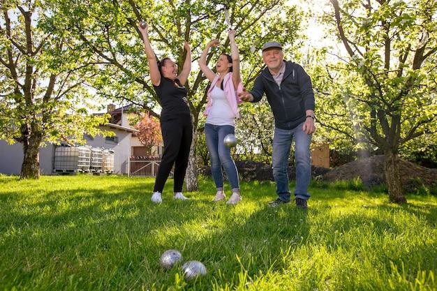 여가 시간을 즐기는 사랑스러운 여름날 외부 정원에서 프랑스 전통 게임 페탕 크를 연주하는 기쁜 긍정적 인 웃는 가족