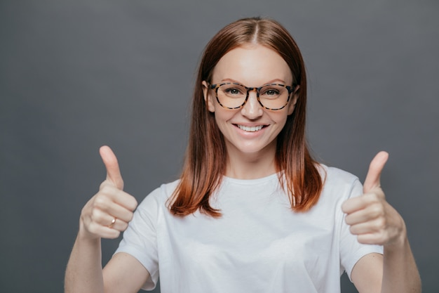 Glad positive woman with tender smile on face, has brown hair, raises two thumbs