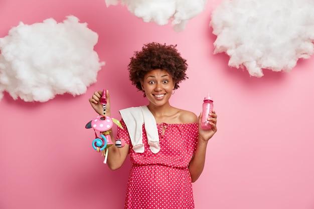 おなかを持つうれしい妊婦は、赤ちゃんのものを保持し、新生児の出産の準備をし、ピンクの壁に隔離された前向きな感情を表現します。幸せな期待、期待、妊娠の概念。