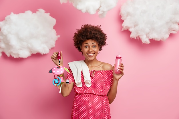 Glad pregnant woman with tummy, holds baby stuff, prepares for newborn birth, expresses positive emotions, isolated on pink wall. happy anticipation, expectation and pregnancy concept.