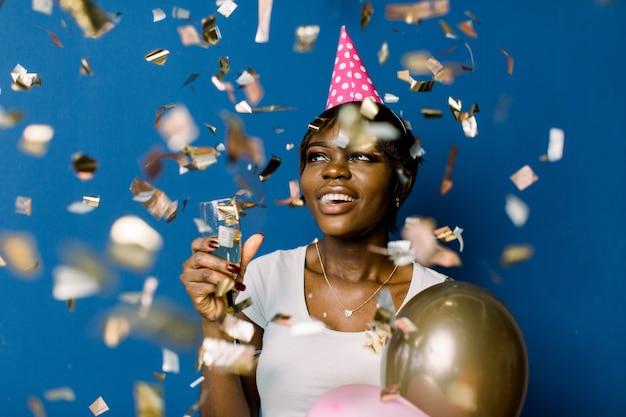 흰색 티셔츠 행복 춤과 색종이 밖으로 던지고, 생일을 축하 다행 꽤 아프리카 여자. 기쁘게 얼굴 표정으로 샴페인과 풍선을 들고 예쁜 흑인 아가씨의 실내 사진