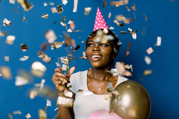 Glad pretty african woman in white t-shirt happy dancing and throwing out confetti, celebrating birthday. indoor photo of pretty black lady holding champagne and balloons with pleased face expression