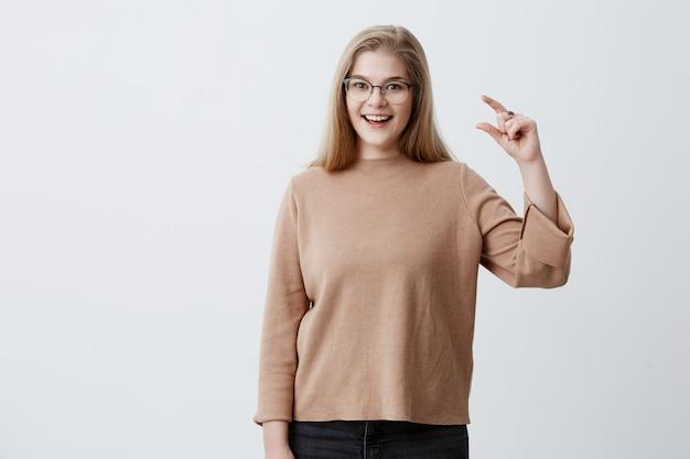眼鏡のかなりブロンドの女性は喜んで手で小さな何かを示し、灰色のスタジオの背景に対して隔離される茶色のセーターを着ています。美しい若い女性は何かのサイズを示します