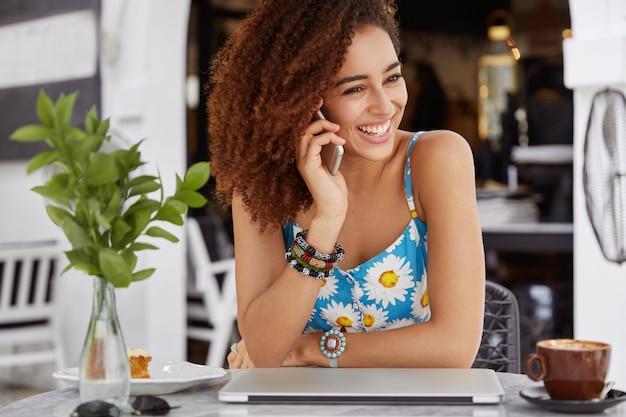 모바일 통화에서 타 리프에 만족하는 기쁘고 꽤 어두운 피부의 여성, 즐거운 일에 대해 이야기하면서 즐겁게 웃습니다.