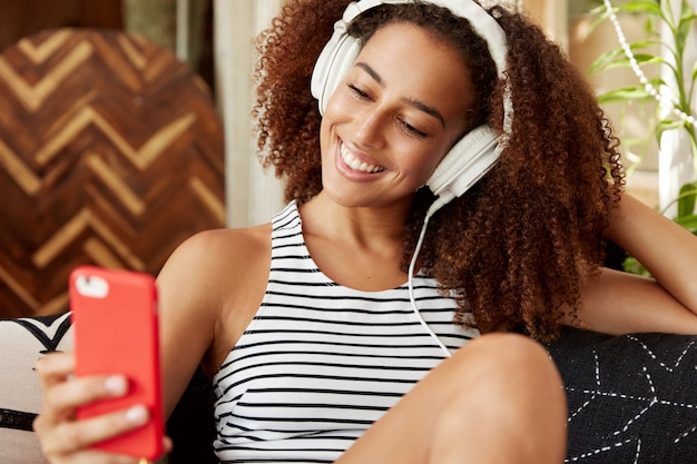 Glad pretty young woman with specific appearance has curly hair and dark skin, poses for selfie, uses modern electronic device and headphones, enjoys leisure time and has positive expression