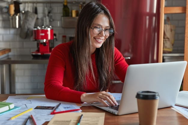 Glad professional brunette female accountant makes distant work, keyboards on laptop computer, sits at kitchen table with papers, wears transparent glasses for good vision, drinks coffee to go