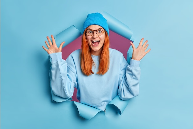 Glad redhead young woman wears optical glasses hat and jumper raises hands stands in torn paper hole excited by great news.