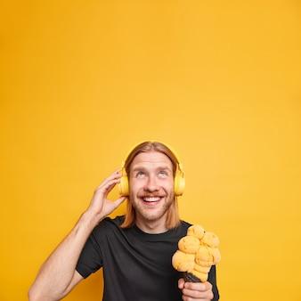 Радостный расслабленный рыжий мужчина смотрит на голову, широко улыбается, держит вкусное мороженое, слушает музыку в наушниках, носит черную футболку, изолированную над ярко-желтой стеной, копируйте пространство для вашего движения