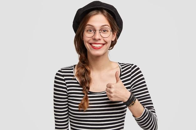 Довольная довольная француженка с привлекательной внешностью поднимает большой палец вверх, показывает ей симпатию и согласие.